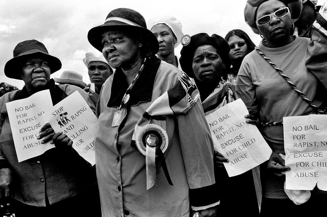 Members of the ANC Women's League hold out flyers that they were distributing at the funeral of 3yr old S'bongile Mokoena who was raped and murdered on November 8, 2003. Soweto, December 2003.