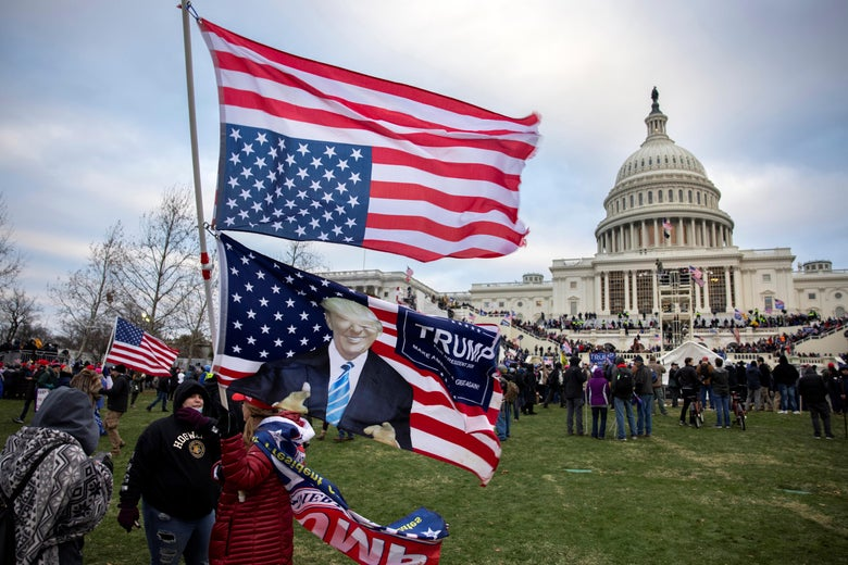 Crowds of people on the lawn and steps of the Capitol. In the foreground, someone holds up an upside-down American flag and a Trump flag.