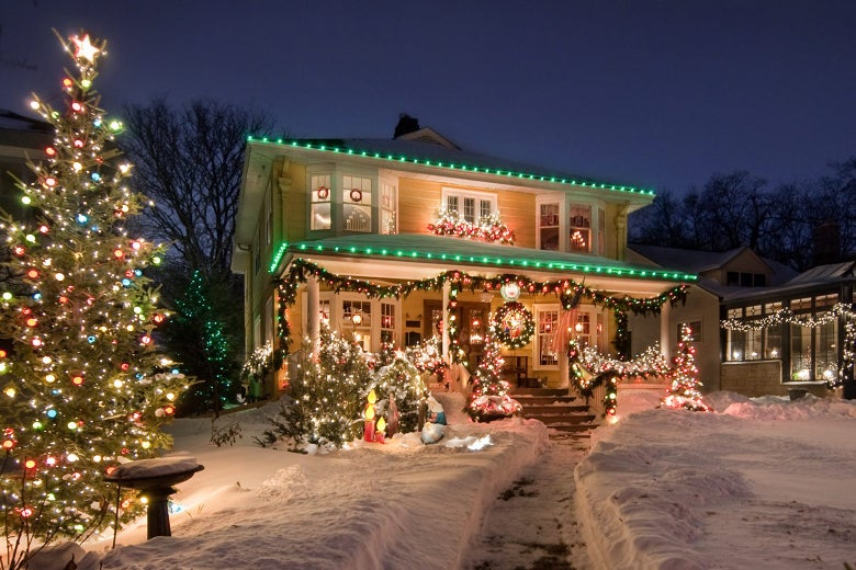 A house with an elaborate holiday light display out front, with multiple Christmas trees on a snow-covered front lawn