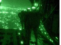 Recon Marines parachute into combat with the lights of Baghdad in the background