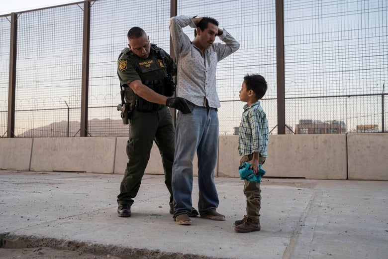 A migrant father has his hands clasped behind his head as a CBP agent searches his pockets. The migrant's son looks on.