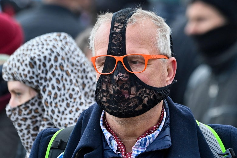 An older man wears black lacy underwear over his face.
