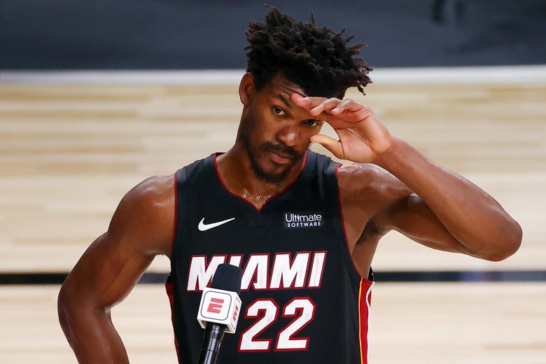 Jimmy Butler in uniform on the court holds a hand to his forehead in front of an ESPN microphone