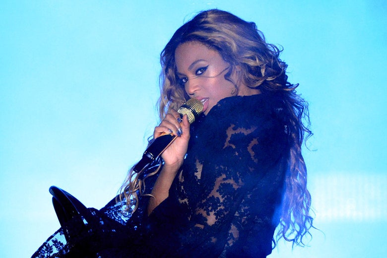 Beyoncé looks over her shoulder, singing into a gold microphone.