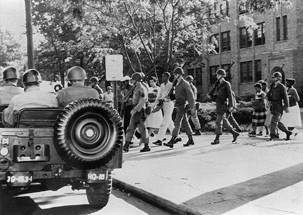 Nine black children are escorted by US paratroopers in full battle dress on September 25, 1957 in Little Rock, Arkansas from Central High School.