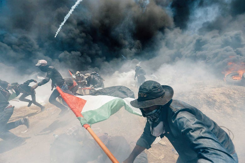 Palestinian demonstrators run for cover from Israeli fire and tear gas during a protest against U.S. embassy move to Jerusalem and ahead of the 70th anniversary of Nakba, at the Israel-Gaza border in the southern Gaza Strip May 14, 2018.
