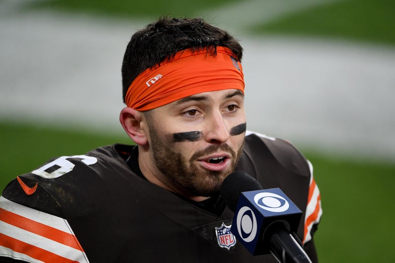 Baker Mayfield in an orange headband and his Browns uniform speaking into a CBS microphone on the field