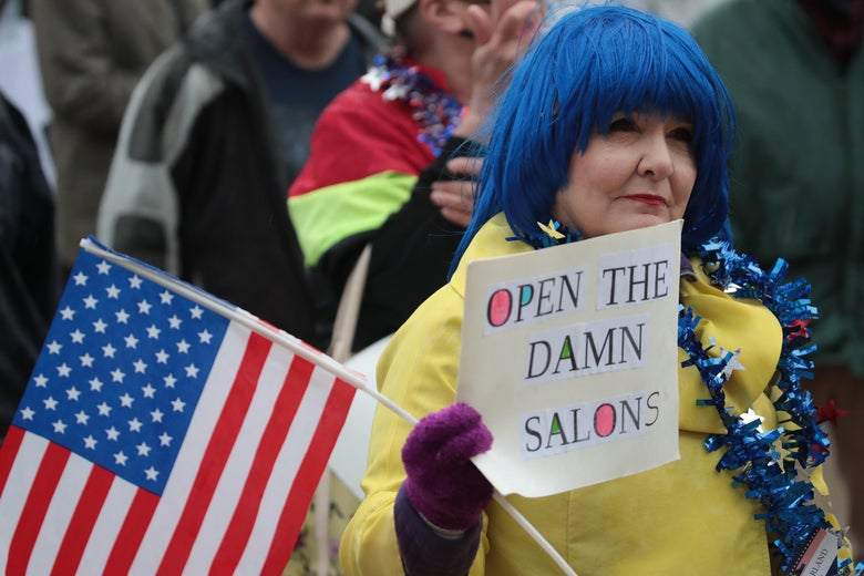 "In a crowd, a woman in blue wig holding an American flag holds up sign that says ""Open the Damn Salons."""