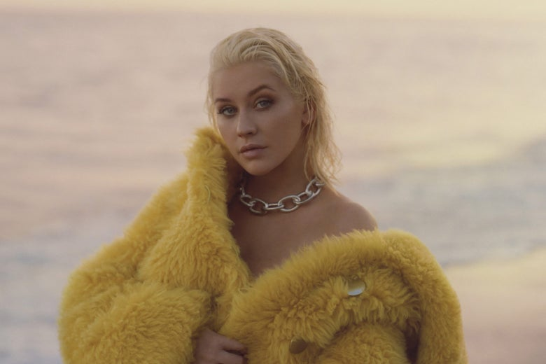Christina Aguilera wears a yellow fur coat off the shoulder.