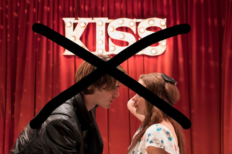 "Jacob Elordi leans in for a kiss from Joey King in front of an illuminated sign reading ""Kiss,"" in this still from The Kissing Booth."