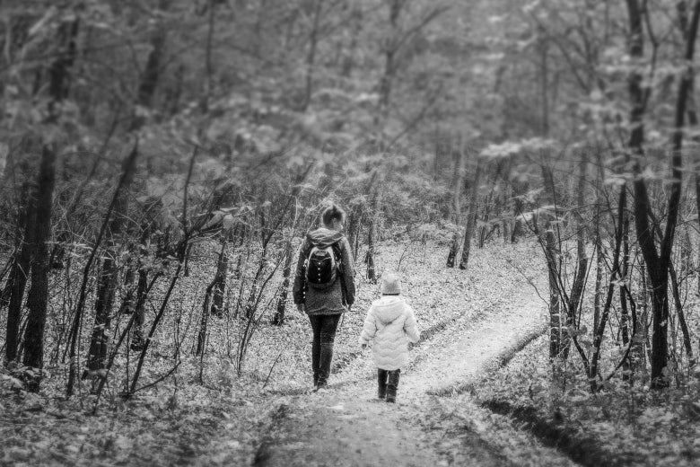 A woman and a child walk through the woods in a black-and-white photo.