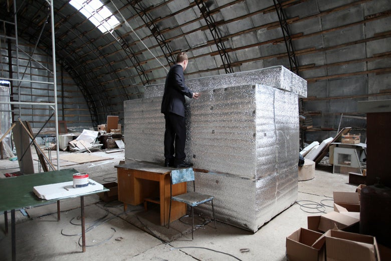 In the center of a cluttered warehouse room, a man stands on a desk to look inside a large silver container.