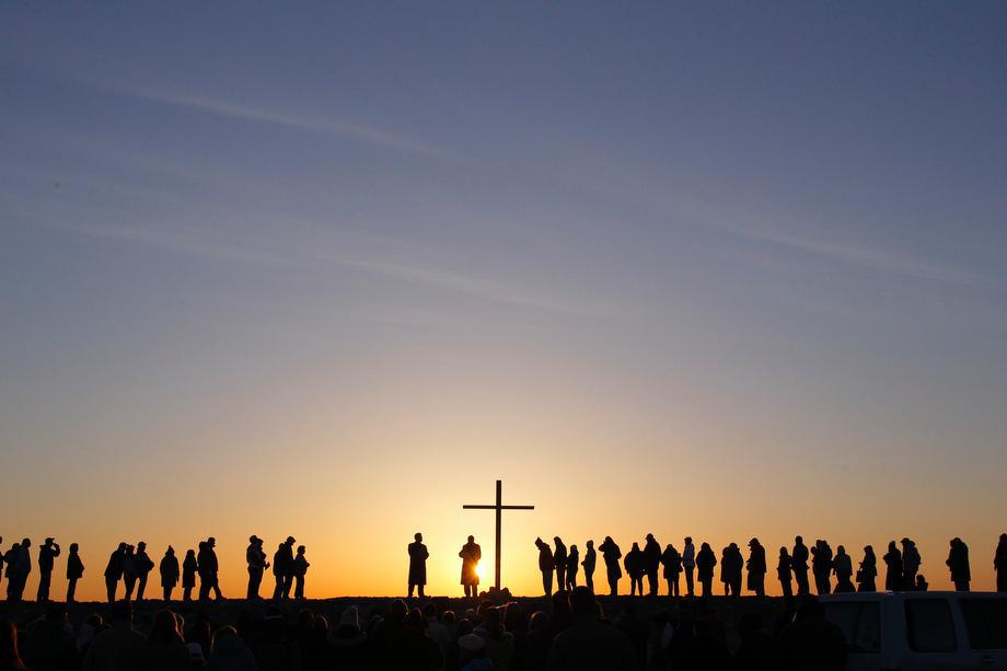People are silhouetted as the sun rises during an Easter sunrise service in Scituate, Massachusetts on March 31, 2013.