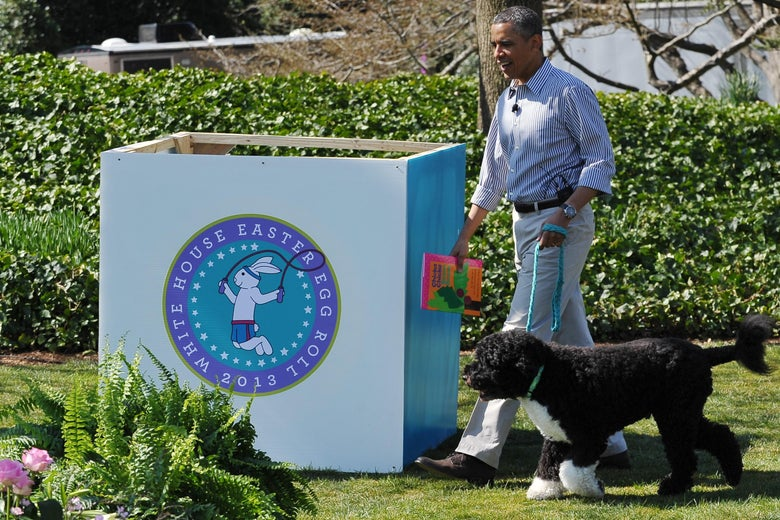 Then-President Barack Obama walks with Bo, the family dog, as he arrives to read a story to children attending the annual Easter Egg Roll on April 1, 2013 on the South Lawn of the White House in Washington, D.C.