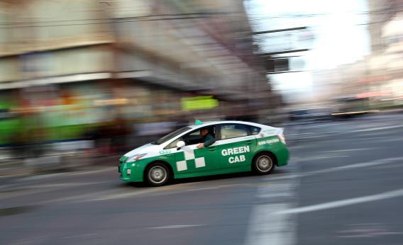 A Toyota Prius hybrid taxi drives across Market Street on in San Francisco