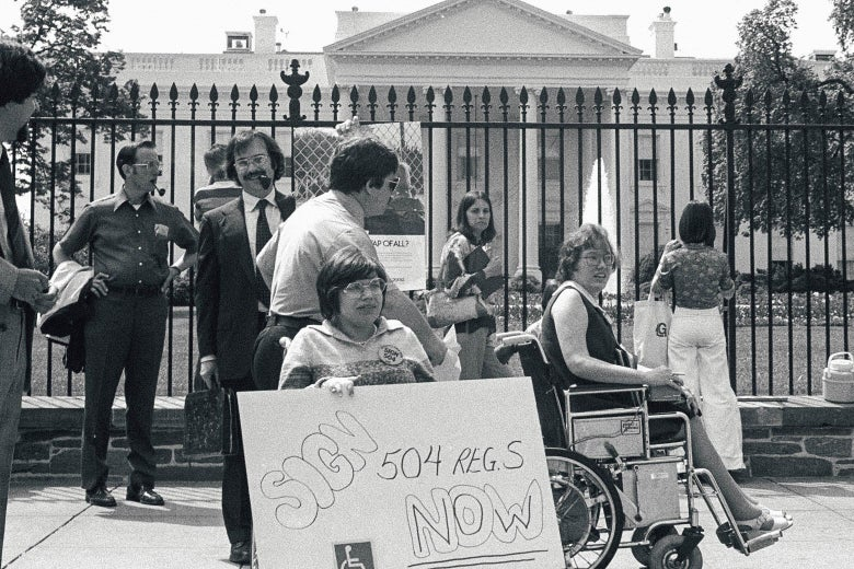 "A black-and-white photo of protestors, some of them in wheelchairs, rallying outside of the White House. One of the signs encourages the president to ""Sign 504 now."""