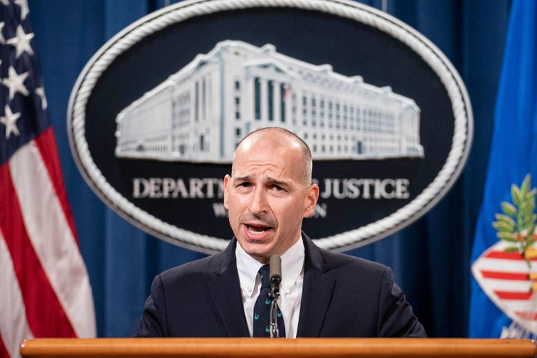 Michael Sherwin, Acting US Attorney for the District of Columbia, speaks at a podium, standing in front of the seal of the Department of Justice and an American flag.