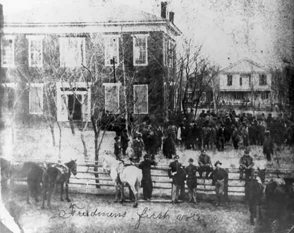 Freedpeople vote for the first time in 1868 at Anderson County Courthouse in Texas. U. S. soldiers stand guard to protect them