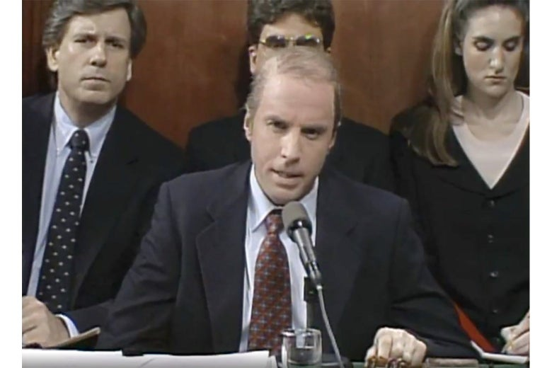 Kevin Nealon as Joe Biden, sitting behind a microphone, on SNL. Three others sit behind him.