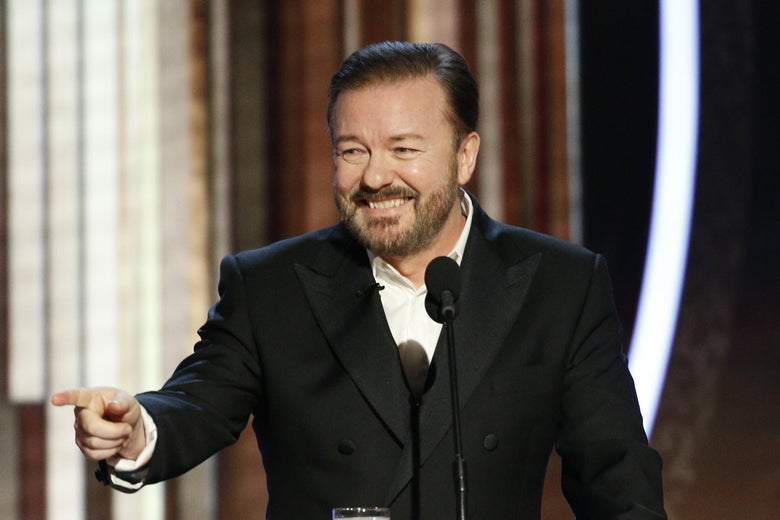 Gervais, standing at a podium, grins and points with his right hand.