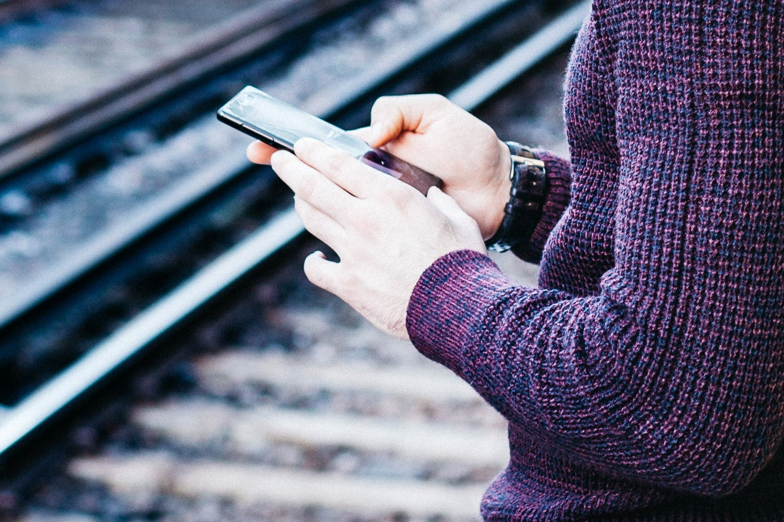A man types on his phone while waiting for a train.
