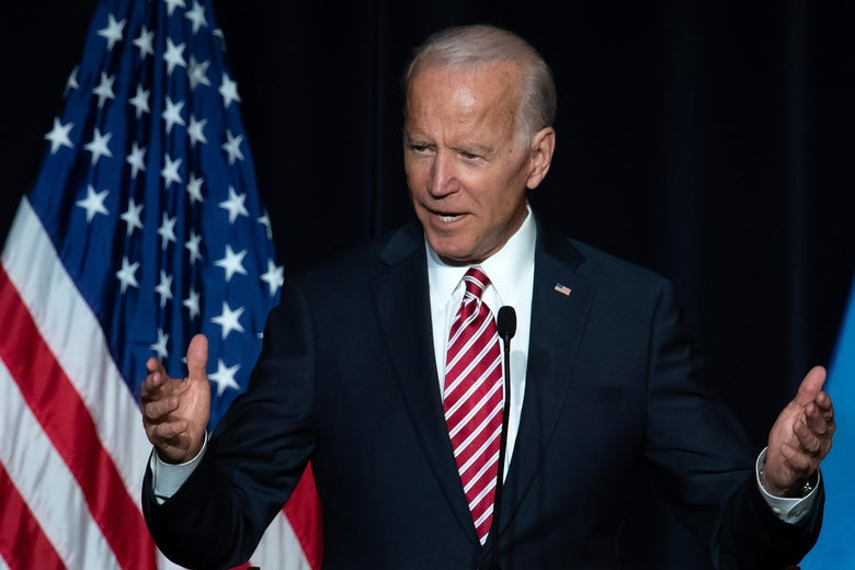 Biden speaking at a mic, arms outstretched, with an American flag behind him.