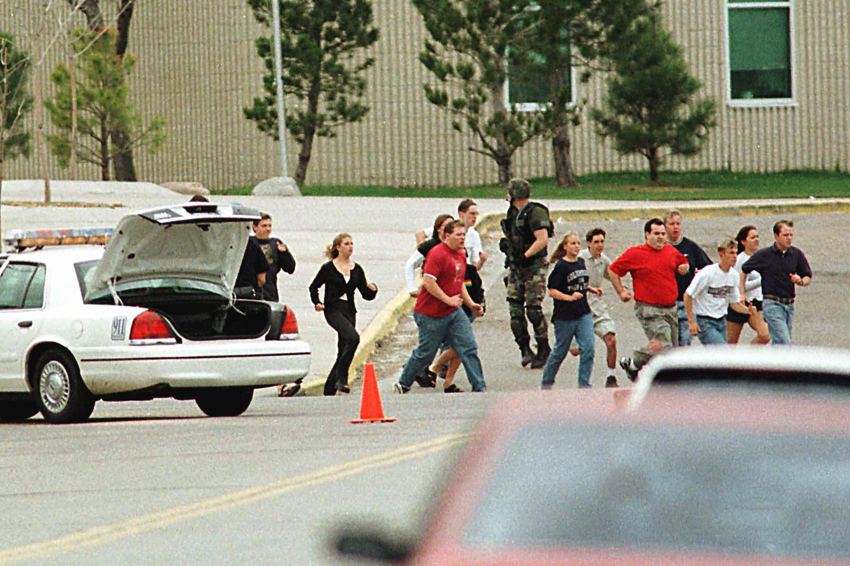 Students run from Columbine High School under cover from police.