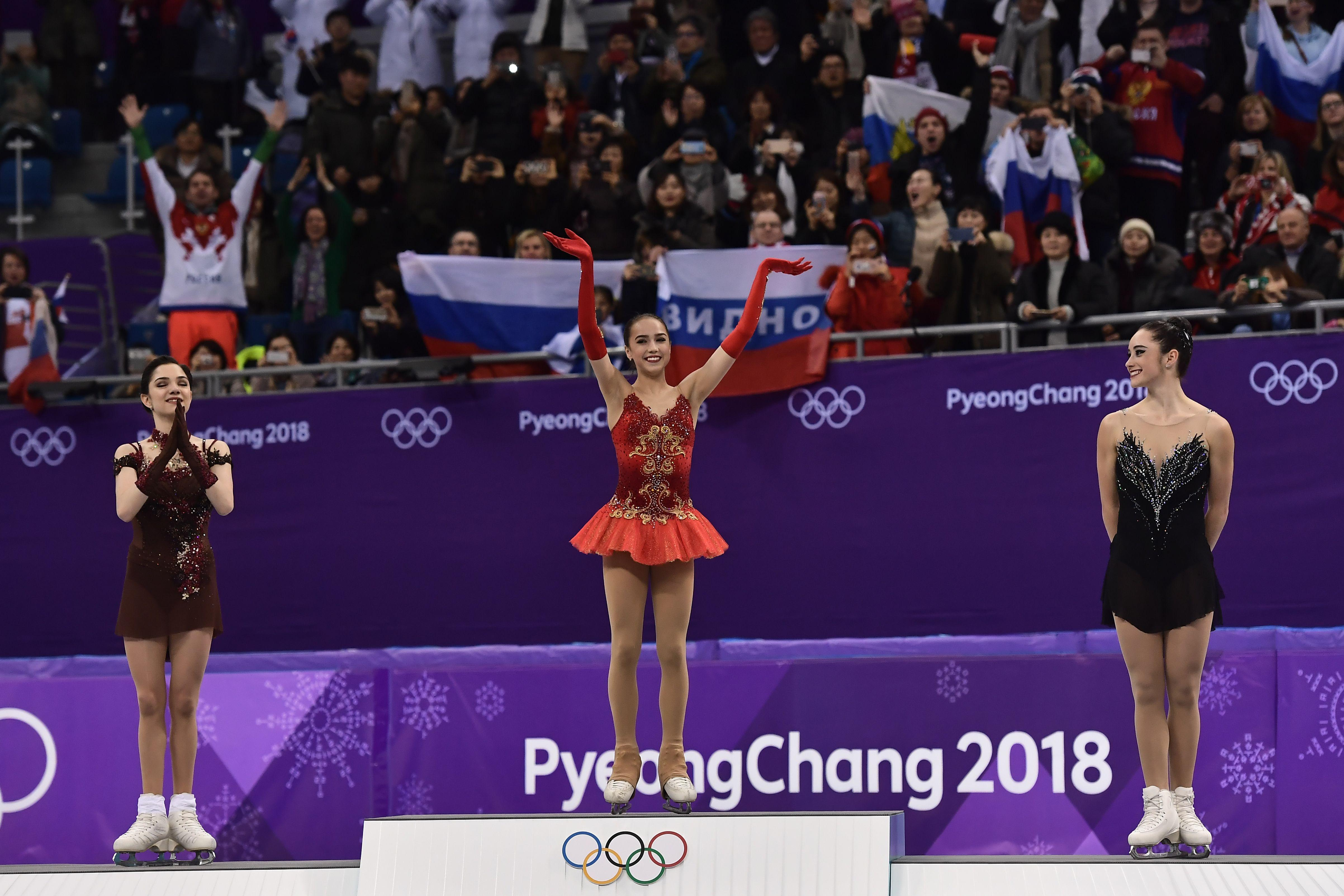 (L-R) Silver medallist Russia's Evgenia Medvedeva, gold medallist Russia's Alina Zagitova and bronze medallist Canada's Kaetlyn Osmond celebrate on the podium during the venue ceremony after the women's single skating free skating of the figure skating event during the Pyeongchang 2018 Winter Olympic Games at the Gangneung Ice Arena in Gangneung on February 23, 2018. / AFP PHOTO / ARIS MESSINIS        (Photo credit should read ARIS MESSINIS/AFP/Getty Images)