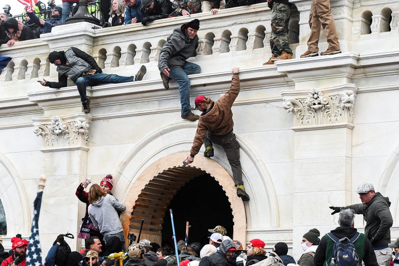 Multiple pro-Trump rioters climb up the walls of the U.S. Capitol while others congregate nearby.