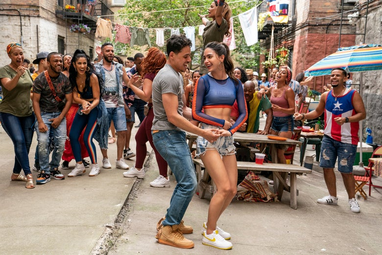 Anthony Ramos and Melissa Barrera dance in front of a crowd on a sidewalk.