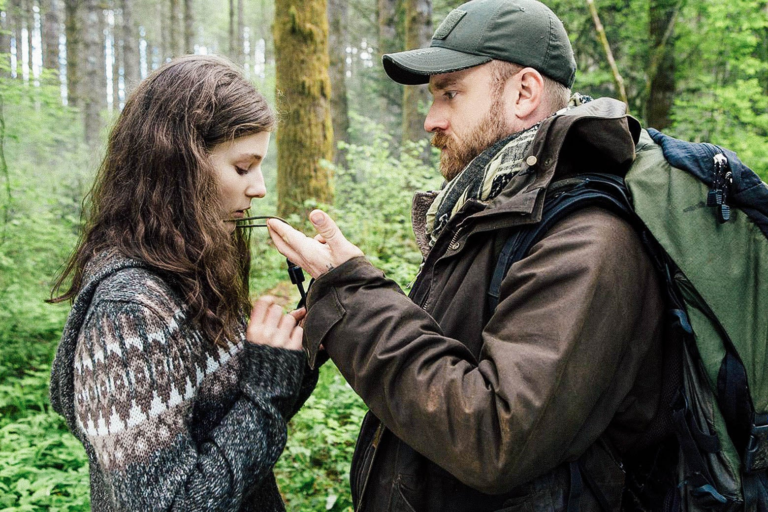 Movie still: Thomasin McKenzie stands while Ben Foster tugs at an object around her neck.