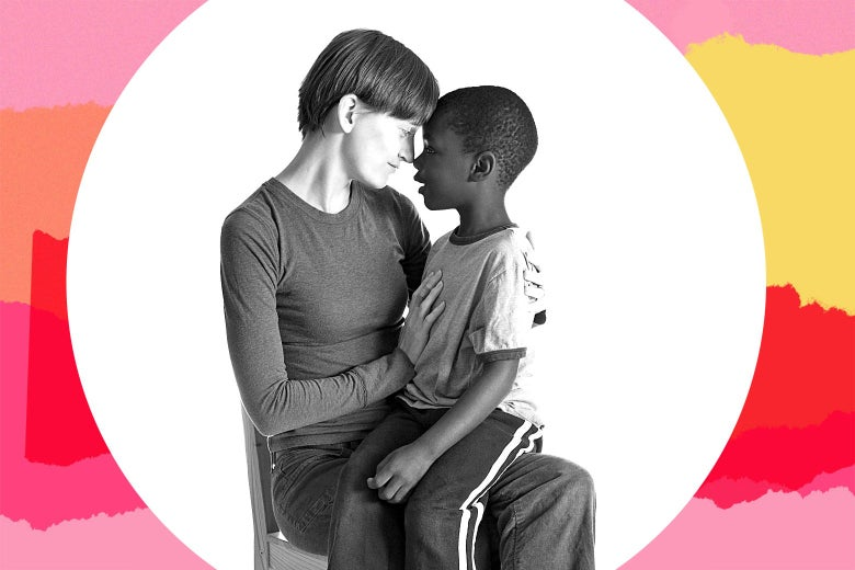 A white woman sitting down, holding a Black child in her lap, their foreheads touching.