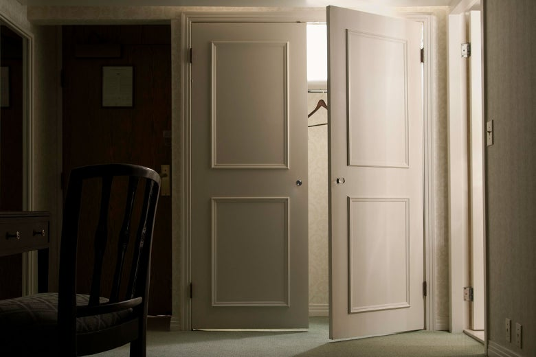 A partially open door to an empty closet.