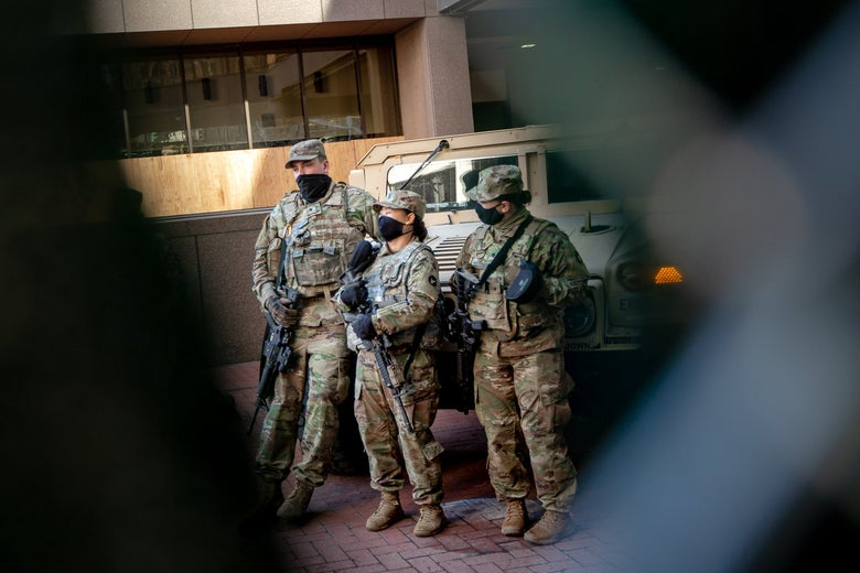 Three National Guard members standing next to an armored vehicle outside the courthouse.