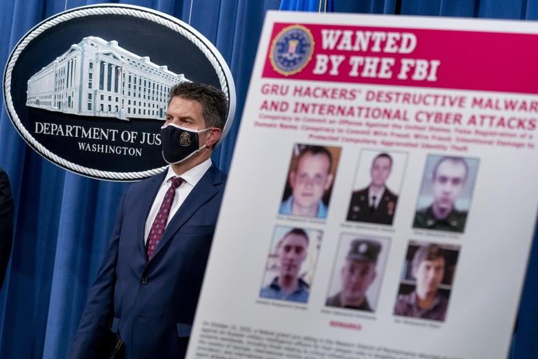 "A poster with six photos says ""Wanted by the FBI"" in front of a man wearing a mask next to the seal of the Department of Justice."