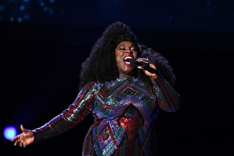 A Black woman in a shiny dress sings into a microphone.