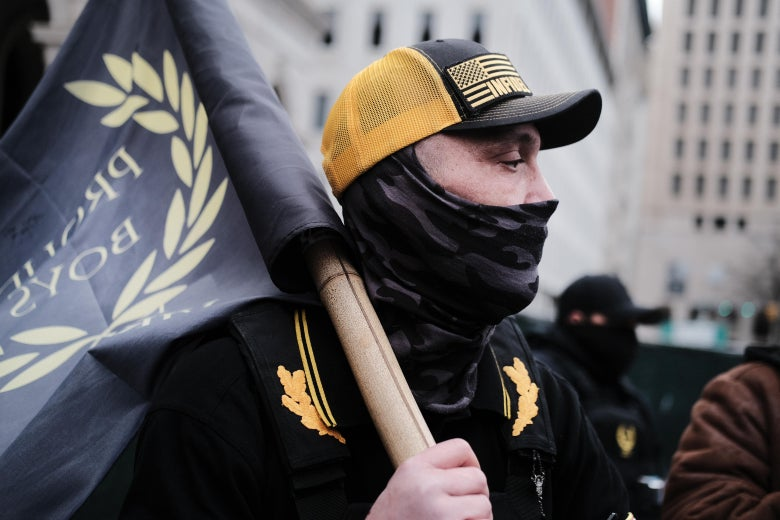 A man in black and yellow clothing carrying a Proud Boys flag.