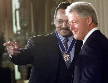 President Bill Clinton (R) presents the Rev. Jesse Jackson (L) with the Presidential Medal of Freedom in the East Room of the White House, August 2000 in Washington, DC.
