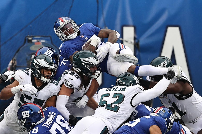 The New York Giants' Wayne Gallman leaps into a pile of Giants and Eagles players.