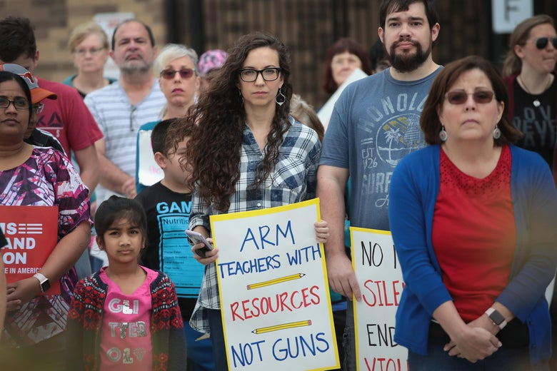 "A woman holds a sign reading, ""Arm teachers with resources not guns."""