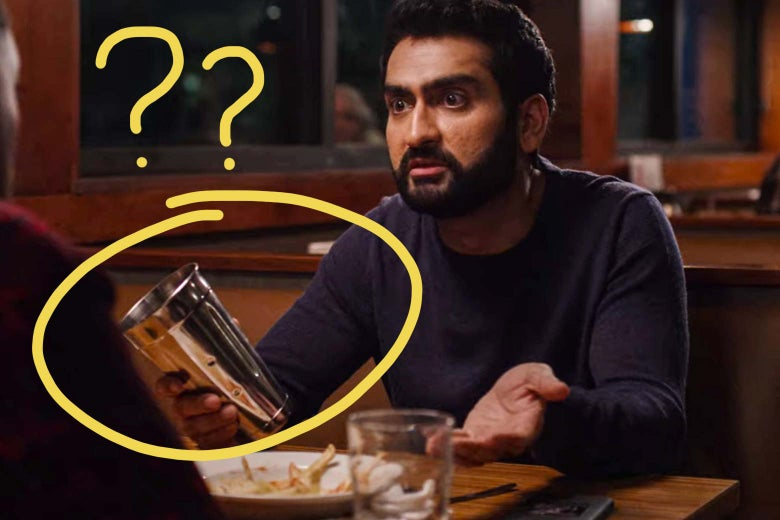 Kumail Nanjiani sitting at a diner booth holding a metal milkshake cup with question marks drawn around it.