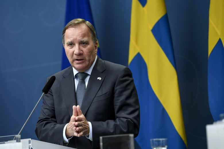 Stefan Löfven stands in front of a Swedish flag and speaks into a microphone while folding his hands.
