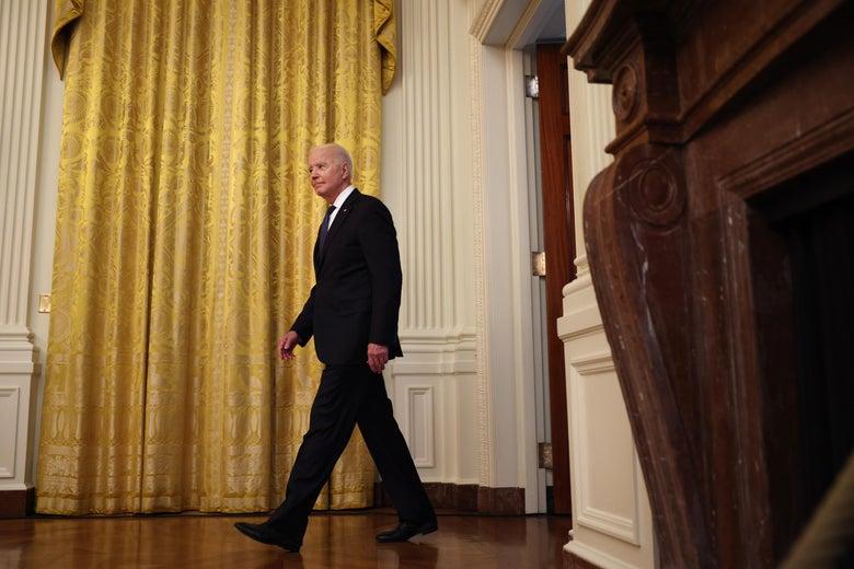 Joe Biden walks into a room in front of a golden curtain.