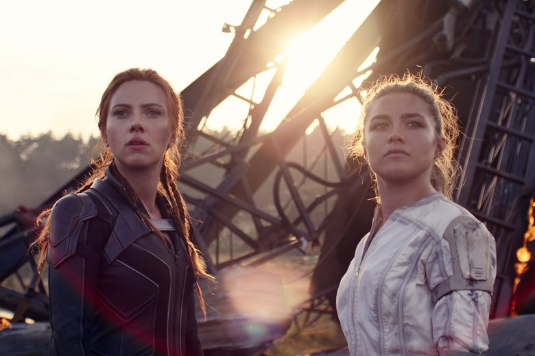 The two women stand in supersuits in front of wreckage, their hair tied back.