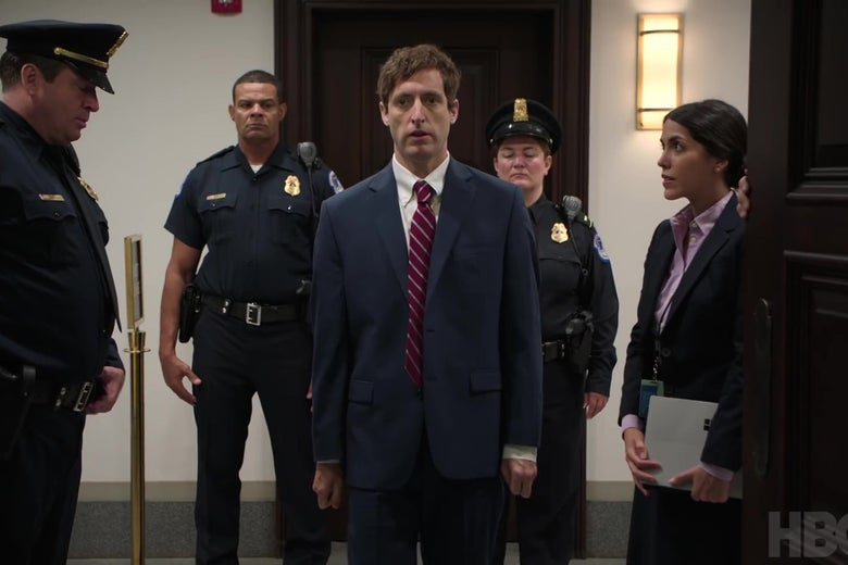 In a still from Silicon Valley, Thomas Middleditch, surrounded by handlers, is about to testify before the Senate.