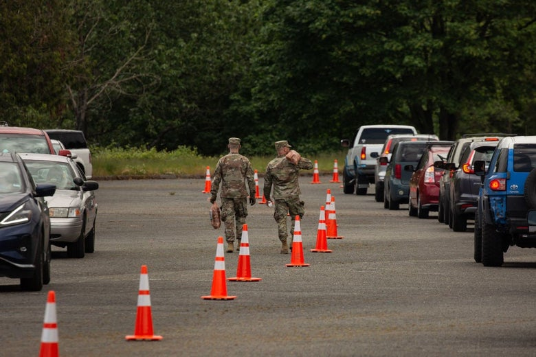Two guard members walk along a line of orange traffic cones between two rows of idling cars.