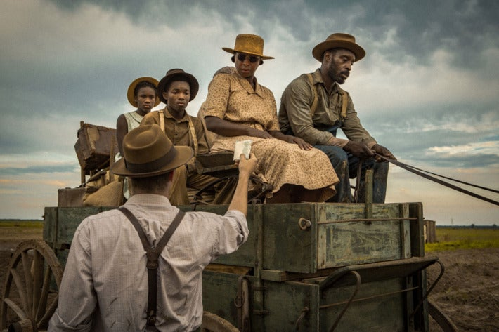 Still from Mudbound showing Jason Mitchell as Ronsel Jackson and Mary J. Blige as Florence Jackson being flagged down while driving a cart.