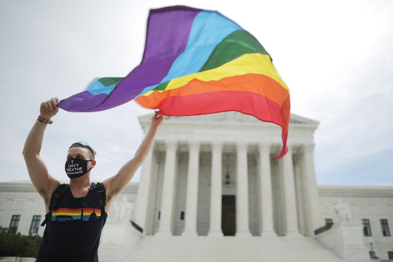 "Fons waves a Pride flag and wears a mask that says ""I can't breathe"" in front of the Supreme Court."