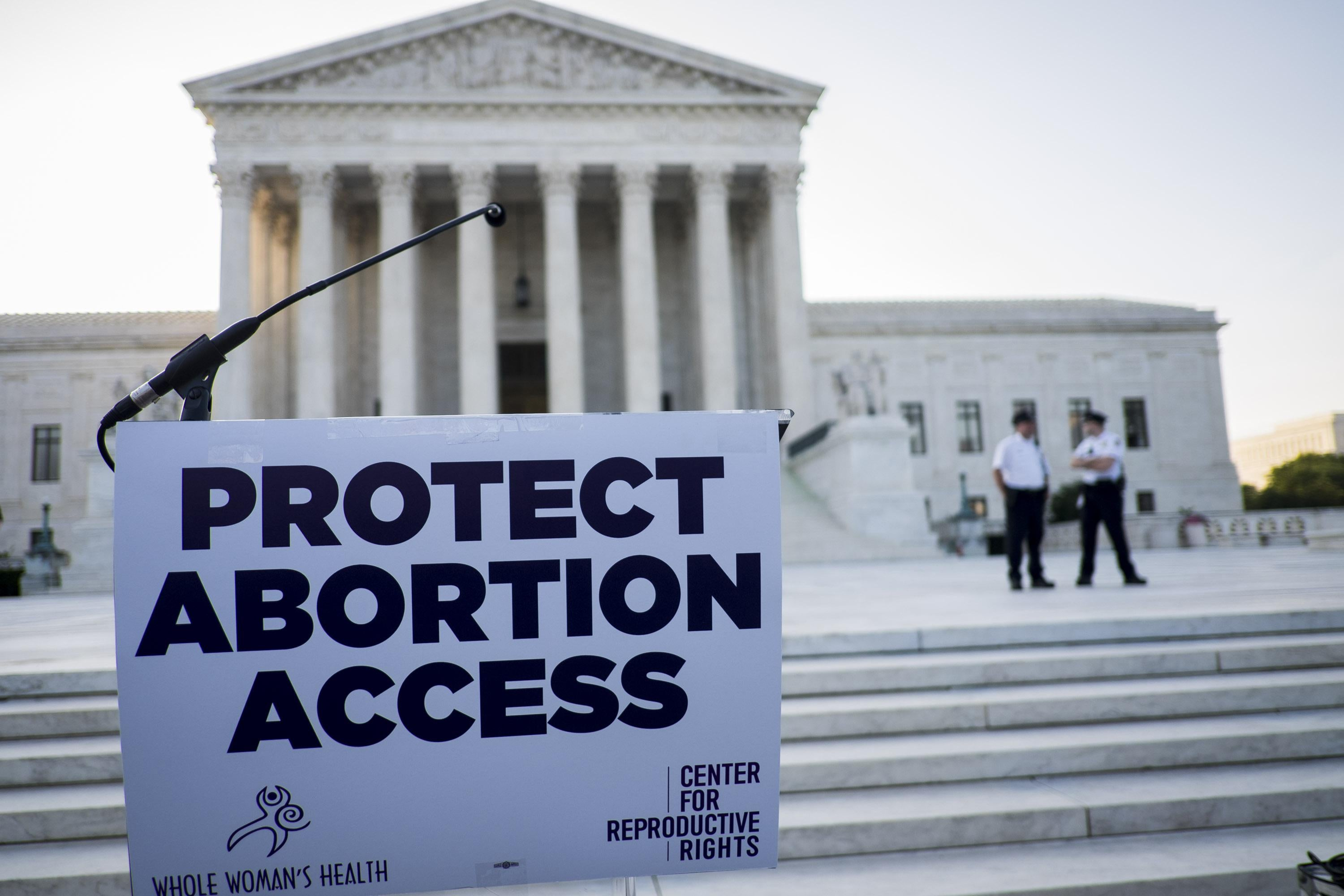 "A protest sign reads, ""Protect Abortion Access,"" on a podium in front of the Supreme Court."
