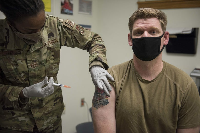 A man in military-green T-shirt and face mask looks at the camera as a woman in fatigues holds a needle near his bicep.